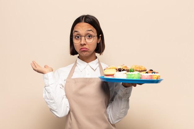 Jonge vrouw die zich in verwarring en verward voelt, twijfelt, weegt of verschillende opties kiest met grappige uitdrukking