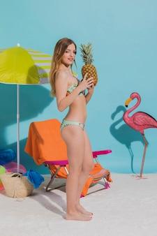 Jonge vrouw die zich met ananas op strand bevindt