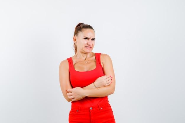 Jonge vrouw die zich met creossed wapens in rood mouwloos onderhemd, broek bevindt en verward, vooraanzicht kijkt.