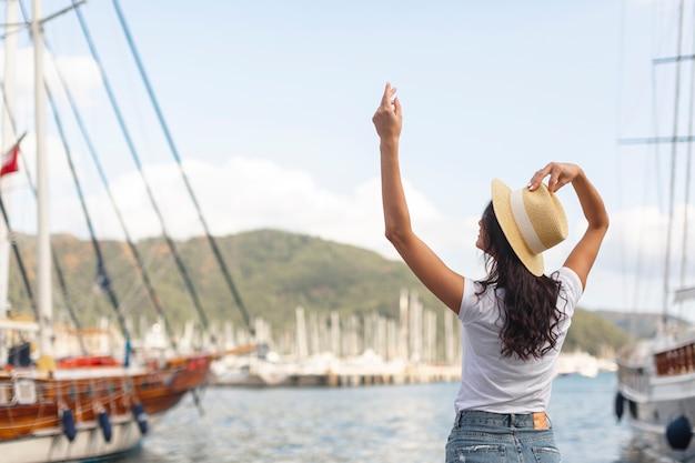 Jonge vrouw die zich met een hand op een haven bevindt