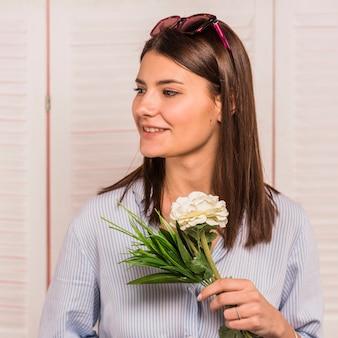 Jonge vrouw die zich met witte in hand bloem bevindt
