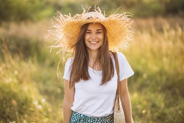 Jonge vrouw die zich met zak in grote hoed op gebied bevindt
