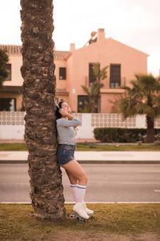 Jonge vrouw die zich onder de boom het luisteren muziek op hoofdtelefoon door de kant van de weg bevindt