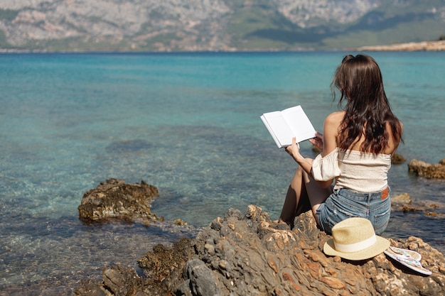 Jonge vrouw die zich op de kust bevindt