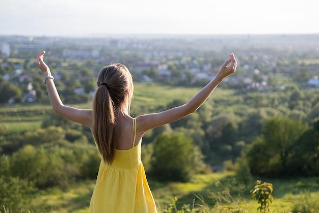 Jonge vrouw die zich op groen gebied bevindt dat van zonsondergangmening in avondaard geniet.