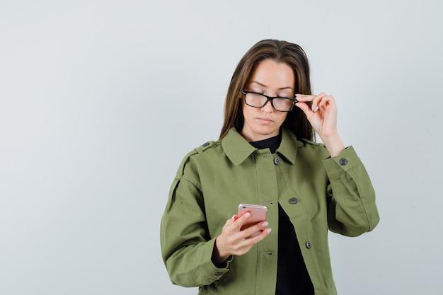 Jonge vrouw die zich op haar mobiele telefoon in groene jas, glazen, vooraanzicht concentreert.
