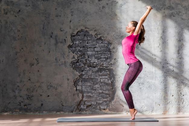 Jonge vrouw die zich op haar tiptoes tegen beschadigde muur bevindt