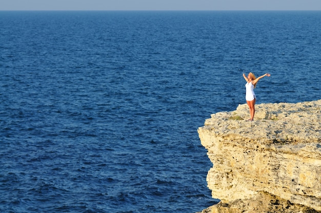 Jonge vrouw die zich op rots over zeewater bevindt en horizon bekijkt
