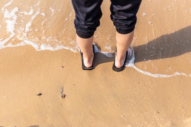 Jonge vrouw die zich op strand met golf over haar voeten bevindt