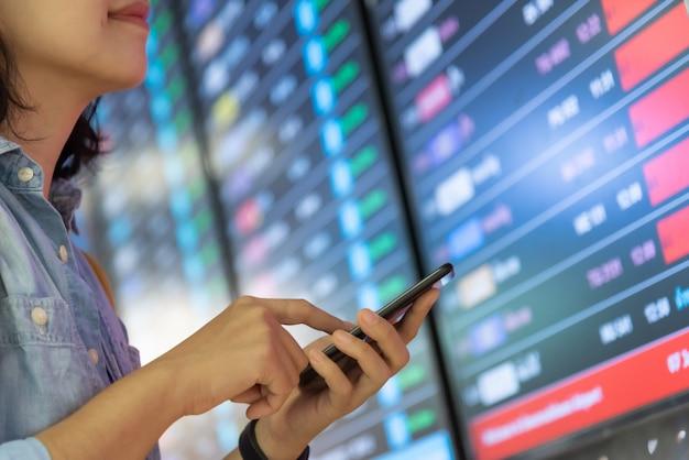 Jonge vrouw die zich over het vluchtinformatiebord bevindt terwijl het gebruiken van smartphone.