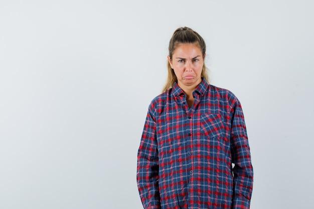 Jonge vrouw die zich rechtop bevindt en aan voorzijde in geruit overhemd stelt en mooi kijkt