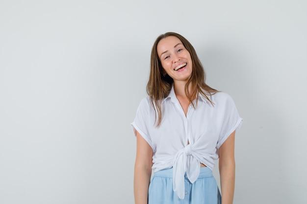 Jonge vrouw die zich rechtop bevindt en in witte blouse en lichtblauwe rok lacht en vrolijk kijkt