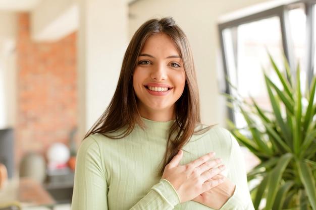 Jonge vrouw die zich romantisch, gelukkig en verliefd voelt, vrolijk glimlachend en hand in hand dicht bij het hart