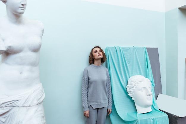 Jonge vrouw die zich tegen een muur bevindt