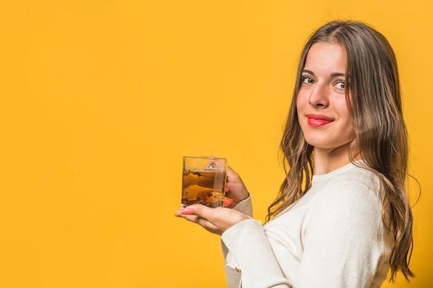 Jonge vrouw die zich tegen gele achtergrond bevindt die aftrekselkop houdt