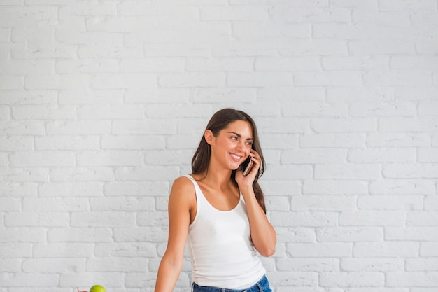 Jonge vrouw die zich tegen witte muur bevindt die op cellphone spreekt