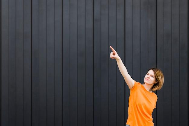Jonge vrouw die zich tegen zwarte muur bevindt die haar vinger naar omhoog richt
