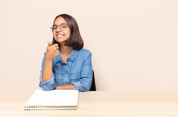 Jonge vrouw die zich trots, zorgeloos, zelfverzekerd en gelukkig voelt, positief glimlacht met omhoog duimen