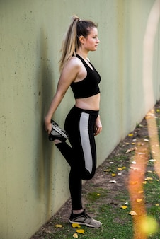Jonge vrouw die zich uitstrekt in de straat