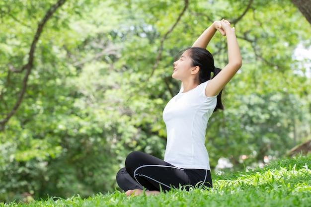 Jonge vrouw die zich uitstrekt in het natuurpark. gezondheidsconcepten.