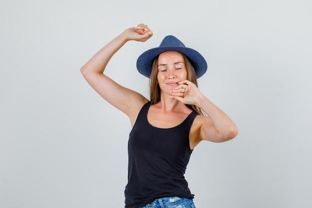 Jonge vrouw die zich uitstrekt lichaam in hemd, korte broek, hoed en op zoek ontspannen