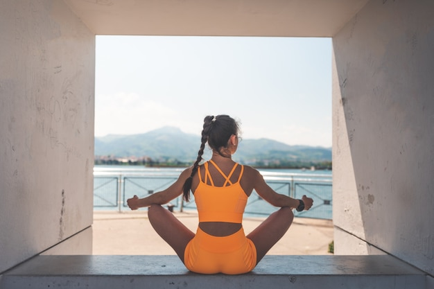 Jonge vrouw die zich uitstrekt met een oranje sport in de haven