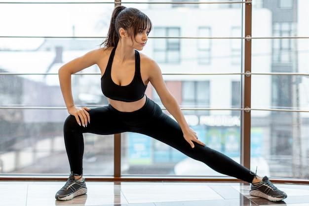 Jonge vrouw die zich uitstrekt voor de training