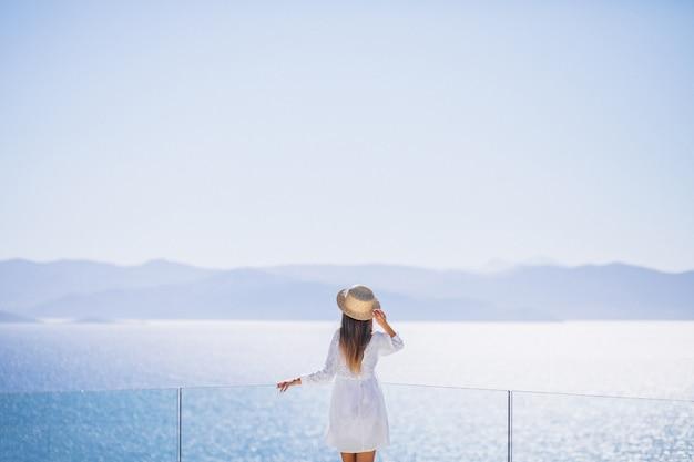 Jonge vrouw die zich van de rug bevindt en de zee bekijkt