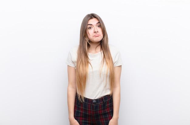 Jonge vrouw die zich verdrietig en gestrest voelt, van streek is vanwege een onaangename verrassing, met een negatieve, angstige blik op een witte muur