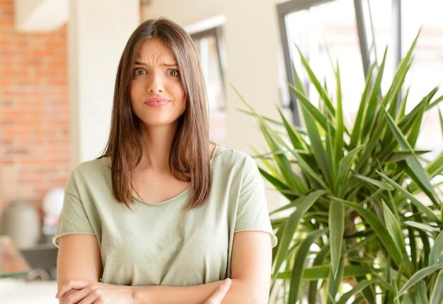Jonge vrouw die zich verward en twijfelachtig voelt en zich afvraagt of probeert te kiezen of een beslissing te nemen