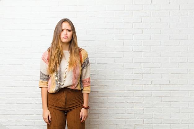 Jonge vrouw die zich verward en twijfelachtig voelt, zich afvraagt of probeert te kiezen of een beslissing neemt