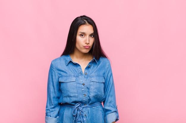 Jonge vrouw die zich verward en twijfelachtig voelt, zich afvraagt of probeert te kiezen of een beslissing te nemen