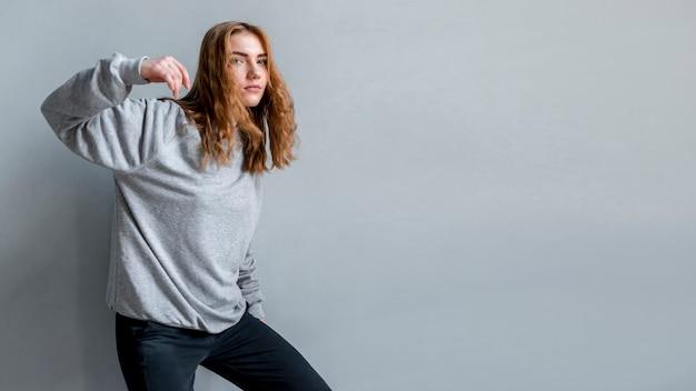 Jonge vrouw die zich voor grijze muur bevindt