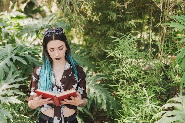 Jonge vrouw die zich voor groeiende installaties bevindt die boek lezen