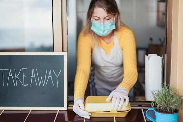 Jonge vrouw die zich voorbereidt om fastfood mee te nemen tijdens de uitbraak van het coronavirus