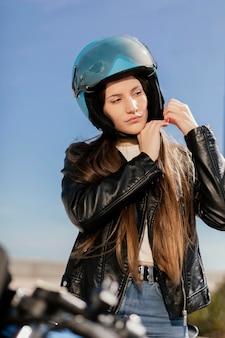Jonge vrouw die zich voorbereidt om in een motorfiets in de stad te rijden