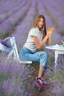 Jonge vrouw die zich voordeed aan tafel in lavendelveld