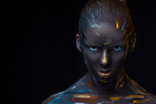 Jonge vrouw die zich voordeed bedekt met zwarte verf
