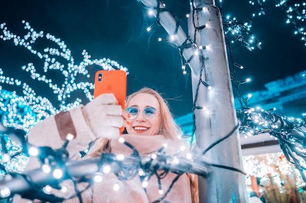 Jonge vrouw die zich voordeed op de straat met verlichte bomen