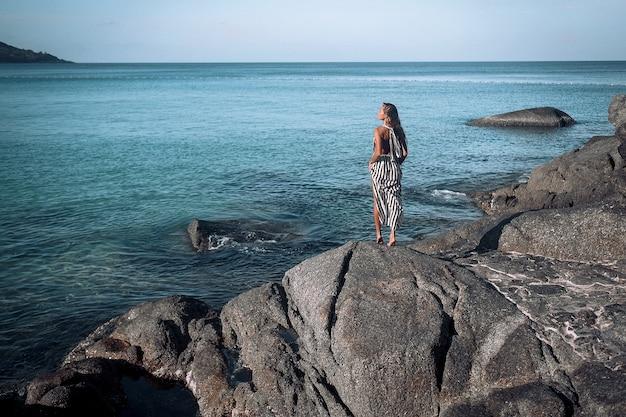 Jonge vrouw die zich voordeed op een strand