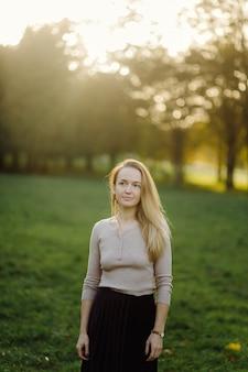Jonge vrouw die zich voordeed op gele bladeren in de herfst park. buitenshuis
