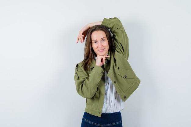 Jonge vrouw die zich voordeed terwijl ze in shirt, jas staat en er delicaat uitziet, vooraanzicht.