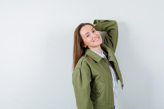 Jonge vrouw die zich voordeed terwijl ze in shirt, jas staat en er gracieus uitziet. vooraanzicht.