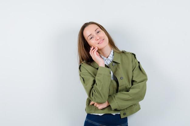 Jonge vrouw die zich voordeed terwijl ze in shirt, jas staat en er mooi uitziet. vooraanzicht.