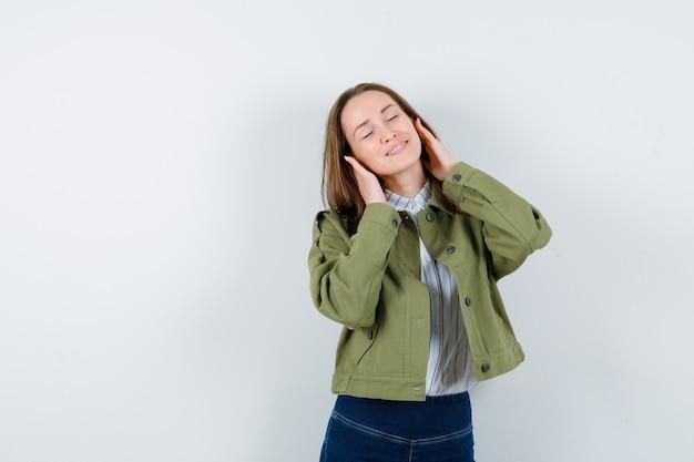 Jonge vrouw die zich voordeed terwijl ze in shirt, jas staat en er vredig uitziet. vooraanzicht.