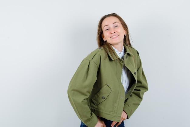 Jonge vrouw die zich voordeed terwijl ze in shirt, jas staat en er zelfverzekerd uitziet. vooraanzicht.