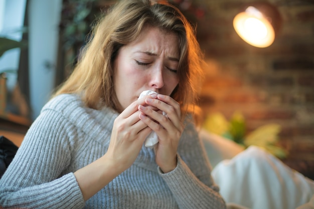 Jonge vrouw die zich ziek voelt - close-up van een hoestend meisje - zieke vrouw die thuis probeert te rusten en te herstellen