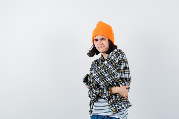 Jonge vrouw die zichzelf omhelst in een geruit overhemd met oranje hoed die er verdacht uitziet