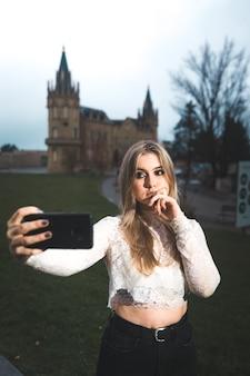 Jonge vrouw die zichzelf opneemt met een mobiele telefoon op straat.