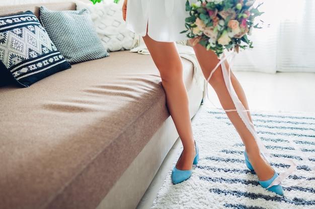 Jonge vrouw die zijdepeignoir en blauwe schoenen draagt en boeket thuis houdt, bruid op huwelijksdag